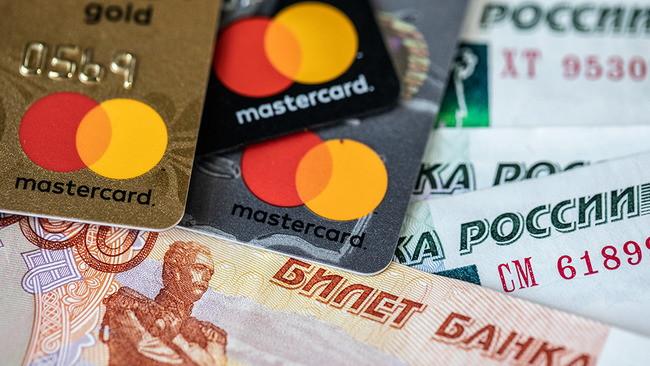 Карты Mastercard на фоне бумажных денег